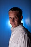 The Man. Young Man with serious look on blue lit background Stock Photo