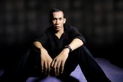Man. Sitting on black background Stock Image