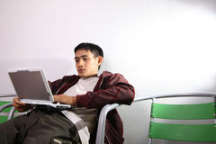 Man. Using netbook on chair Royalty Free Stock Photo
