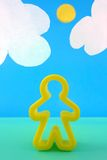 Man. The yellow form of the little man against the sky and clouds from a paper Royalty Free Stock Photography