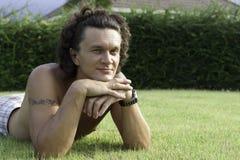 The man. Lies on a green grass Stock Photography