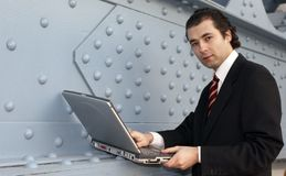 Man. In grey suit, with laptop Stock Images