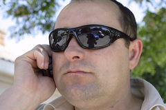 Man. Speaks on telephone. Bespectacled photographer is reflected Royalty Free Stock Photo