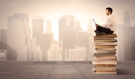 Man above the city sitting on books. A serious businessman with laptop tablet in elegant suit sitting on a stack of books in front of cityscape Stock Images