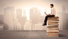 Man above the city sitting on books. A serious businessman with laptop tablet in elegant suit sitting on a stack of books in front of cityscape Royalty Free Stock Photography