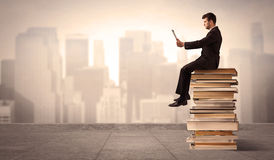 Man above the city sitting on books. A serious businessman with laptop tablet in elegant suit sitting on a stack of books in front of cityscape Stock Photography