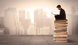 Man above the city sitting on books. A serious businessman with laptop tablet in elegant suit sitting on a stack of books in front of cityscape Royalty Free Stock Image