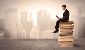 Man above the city sitting on books Stock Photos