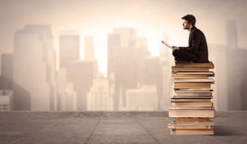 Man above the city sitting on books. A serious businessman with laptop tablet in elegant suit sitting on a stack of books in front of cityscape Stock Image