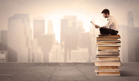 Man above the city sitting on books Stock Images