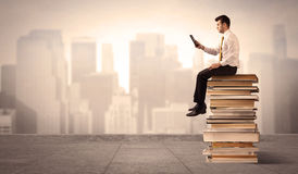 Man above the city sitting on books. A serious businessman with laptop tablet in elegant suit sitting on a stack of books in front of cityscape Stock Photos