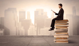 Man above the city sitting on books Royalty Free Stock Image