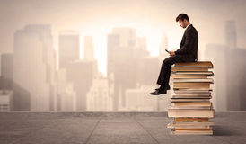 Man above the city sitting on books. A serious businessman with laptop tablet in elegant suit sitting on a stack of books in front of cityscape Stock Photo