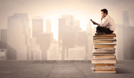 Man above the city sitting on books Stock Image