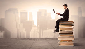 Man above the city sitting on books. A serious businessman with laptop tablet in elegant suit sitting on a stack of books in front of cityscape Royalty Free Stock Photos