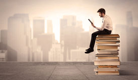 Man above the city sitting on books Stock Photography