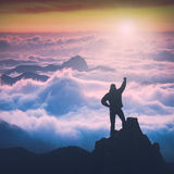 Man above the high mountain valley. Instagram stylization. Man standing on a cliffs edge with raised hand against mountain valley covered with fog in a light of Royalty Free Stock Image