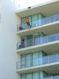 Man abseiling on highrise building. Worker abseiling on highrise apartments to make repairs Royalty Free Stock Images