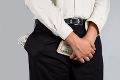 Man with abundant of money in his pockets and holding some money. Man in smart casual dressing with his pockets filled with cash while also holding some notes Stock Images
