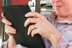 Man accessing internet using his electronic tablet. Hand of a man while busy operating his electronic tablet stock image