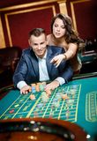 Man accompanied by woman at the casino table Royalty Free Stock Images