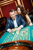 Man accompanied by woman at the roulette table. Man accompanied by women placing bets at the roulette table stock image