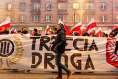 Independence Day March in Warsaw Poland Marred by Violence and Controversy. A man accompanies a nationalist banner as protesters wave flags at the annual Polish Royalty Free Stock Images