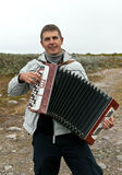 Man with an accordion. In the background of the Barents Sea royalty free stock image