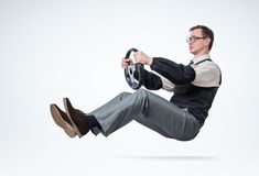 Man accountant with glasses and sleeves is driving a car with steering wheel. Driver concept stock photos