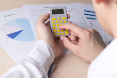 Man accounting something with calculator Stock Images