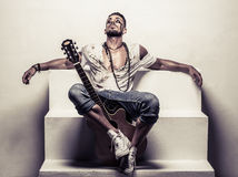 Man with Acoustic Guitar Relaxing on Steps Stock Photography