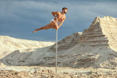 Man is an acrobat on a pole. Man is an acrobat on a pole, he performs tricks Stock Image