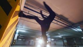 Man acrobat shows tricks somersault at underground parking. Wide angle stock footage
