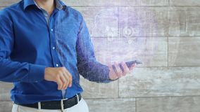 Man activates a conceptual hologram with satellite in the center. The guy in the blue shirt and light trousers with a holographic screen on the background of stock video