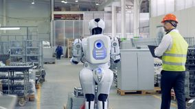 A man activates droid at a factory. A worker switches on a robot to make it pull a heavy cart with metal sheets.