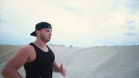 A man actively runs in order to develop endurance and maintain a physical form. A man who goes in for sports runs through the sand park in order to perform stock footage