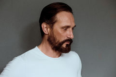 Man actor on grey background with severe face. Beardy mature male in white t-shirt on casting in studio Stock Photo