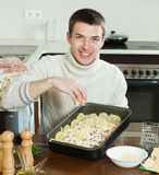 Man adding grated cheese in roasting pan Royalty Free Stock Images
