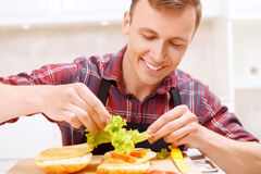 Man adding lettuce leaves  to his sandwich Royalty Free Stock Photography