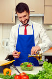 Man adding olive oil in salad Stock Photo