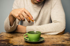 Man adding sugar to his coffee or tea royalty free stock image