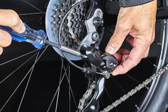 Man adjusting bicycle derailleur gear with tools Closeup Stock Photography