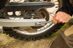 Man adjusting bolts with socket wrench on rear motorcycle wheel. Man adjusting bolt with socket wrench on rear motorcycle wheel. Bike rider fixing his ride by stock photos