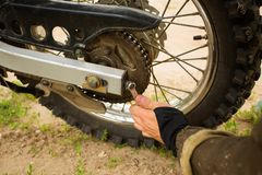 Man adjusting bolts with socket wrench on rear motorcycle wheel. Man adjusting bolt with socket wrench on rear motorcycle wheel. Bike rider fixing his ride by royalty free stock photography