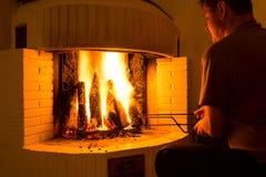 Man adjusting firewood Royalty Free Stock Photography