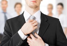 Man adjusting his tie Stock Images