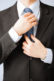 Man adjusting his tie Stock Image