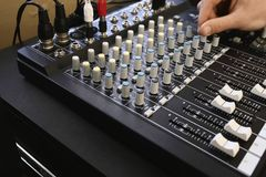 Man adjusting knob on mixing console close-up. Stock Images