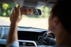 Man adjusting mirror in car Royalty Free Stock Images