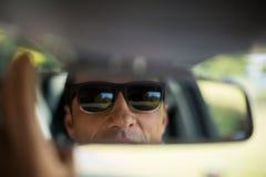 Man adjusting mirror in car Royalty Free Stock Photos
